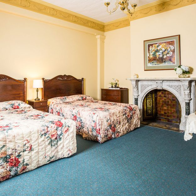 twin beds and stunning wall decors featured in one of Avonmore on the Park's rooms